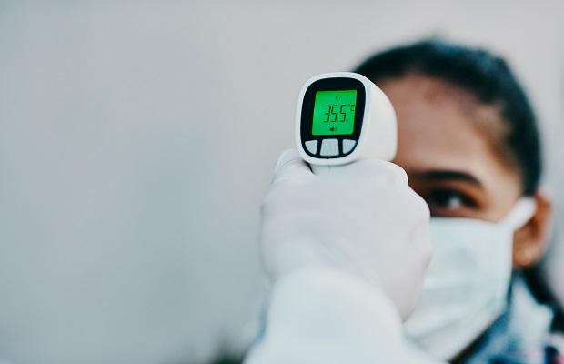 Nhân viên an ninh kiểm tra đo nhiệt độ và rửa tay với gel sát khuẩn